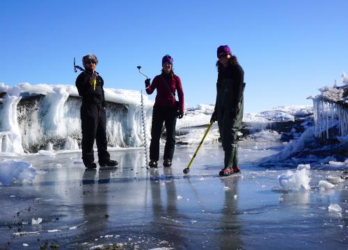 Three researchers stand on a frozen meltwater lake in Antarctica. Photo: Alison Banwell/CIRES