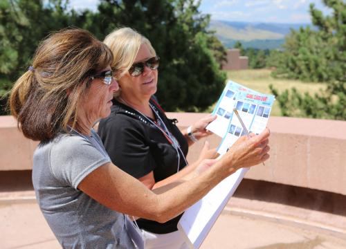 two teachers at workshop outdoors confer on charts