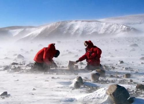 Two scientists in large red parkas kneeling on the ground working on scientific equipment in a snowy landscape while a cold wind whips snow up around them.