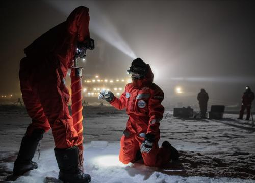 MOSAiC scientists drill through the Arctic ice with the research vessel Polarstern illuminated in the background.