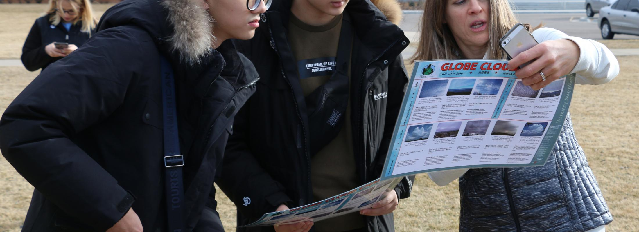 Chinese students look at chart held by an instructor outdoors