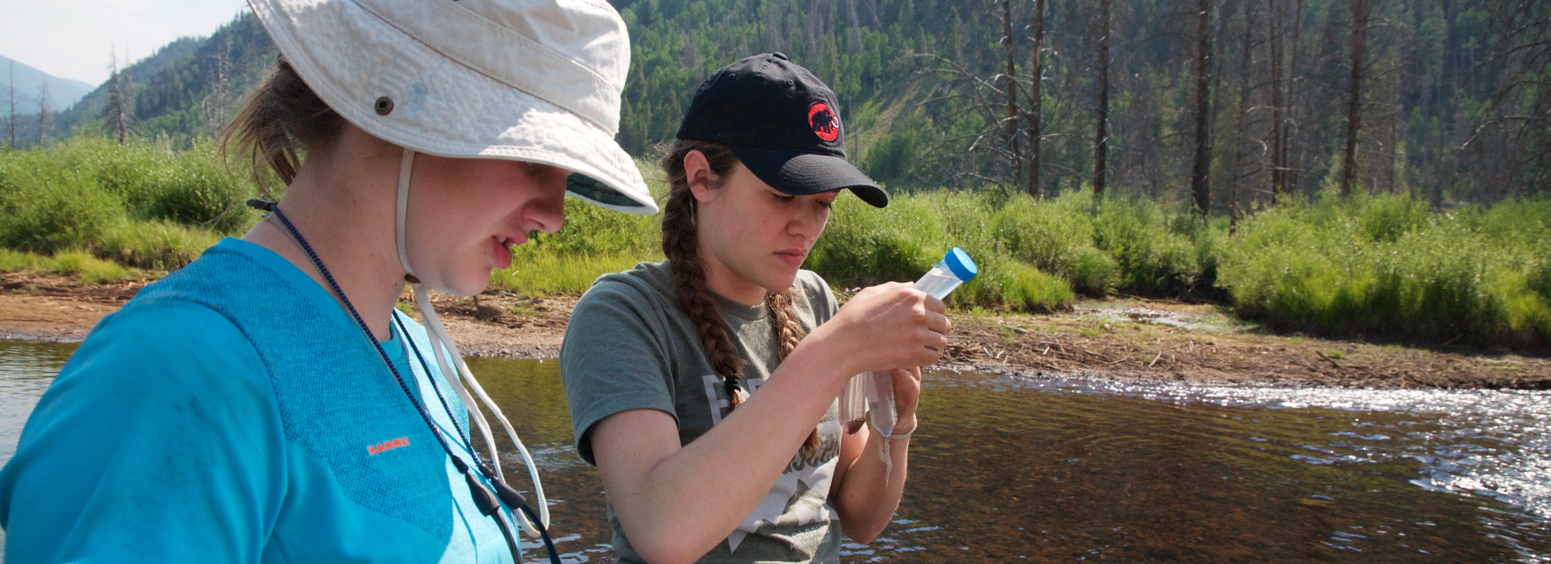 Two young female students stand in a river taking water samples.
