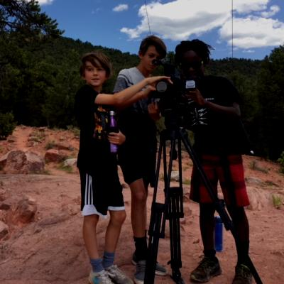Three boys line up a shot on a video recorder.