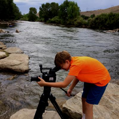 A boy uses a video camera in front of a river.
