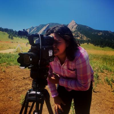 A girl films a video in front of the Boulder Flatirons.