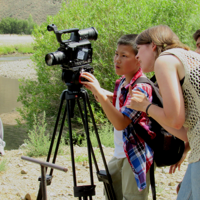 A mentor helps a child line up a shot on a video camera.