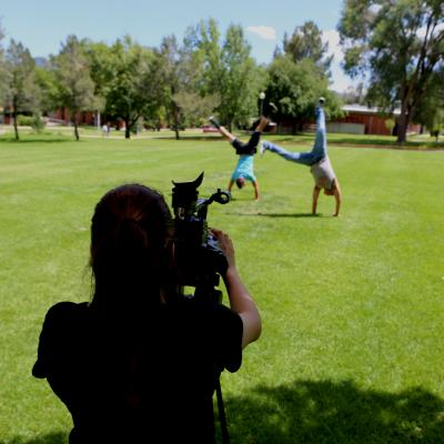 A student films other children doing cartwheels while a mentor looks on.