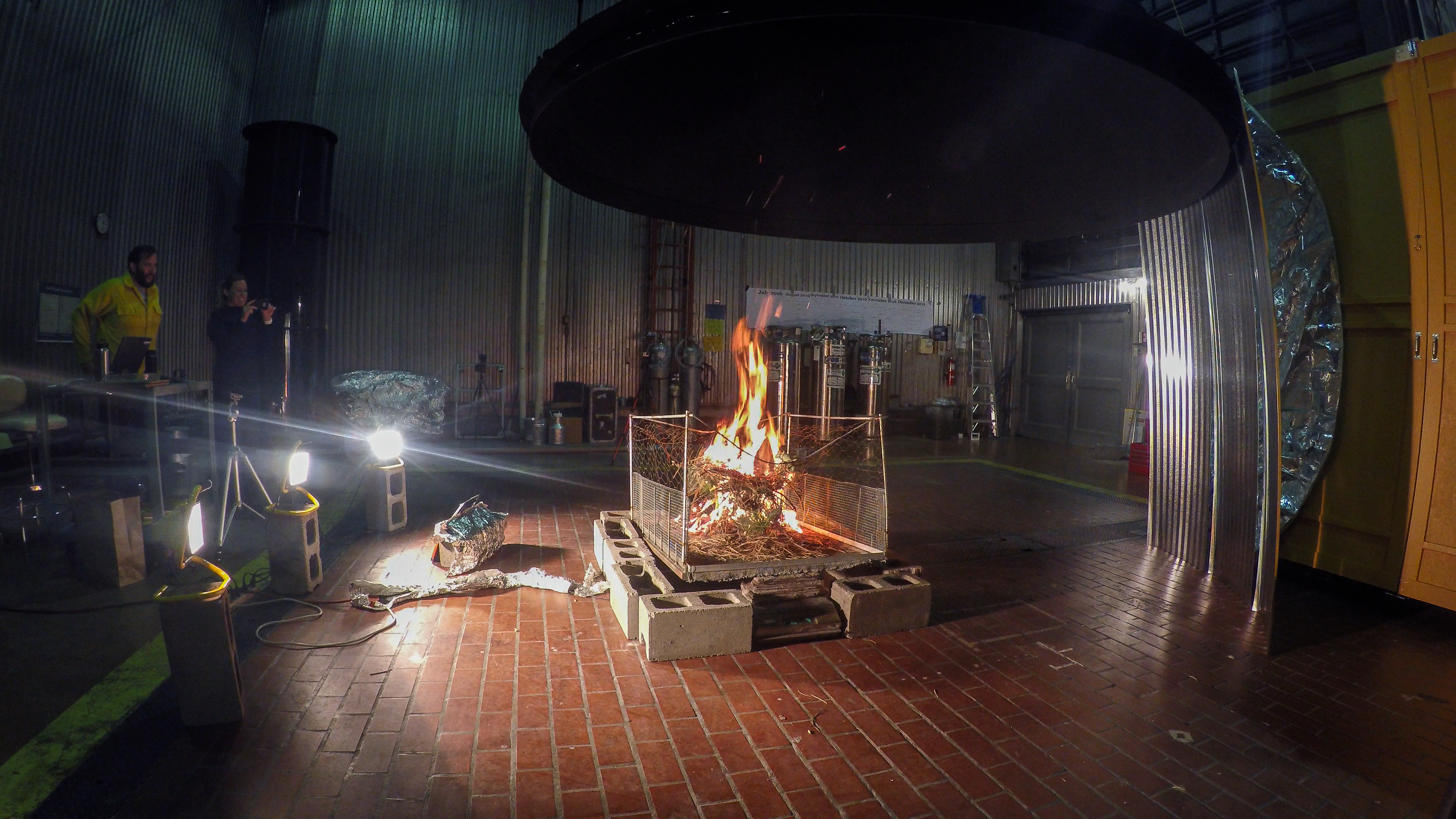 Photo of fire burning in a lab with instruments to sample fire emissions