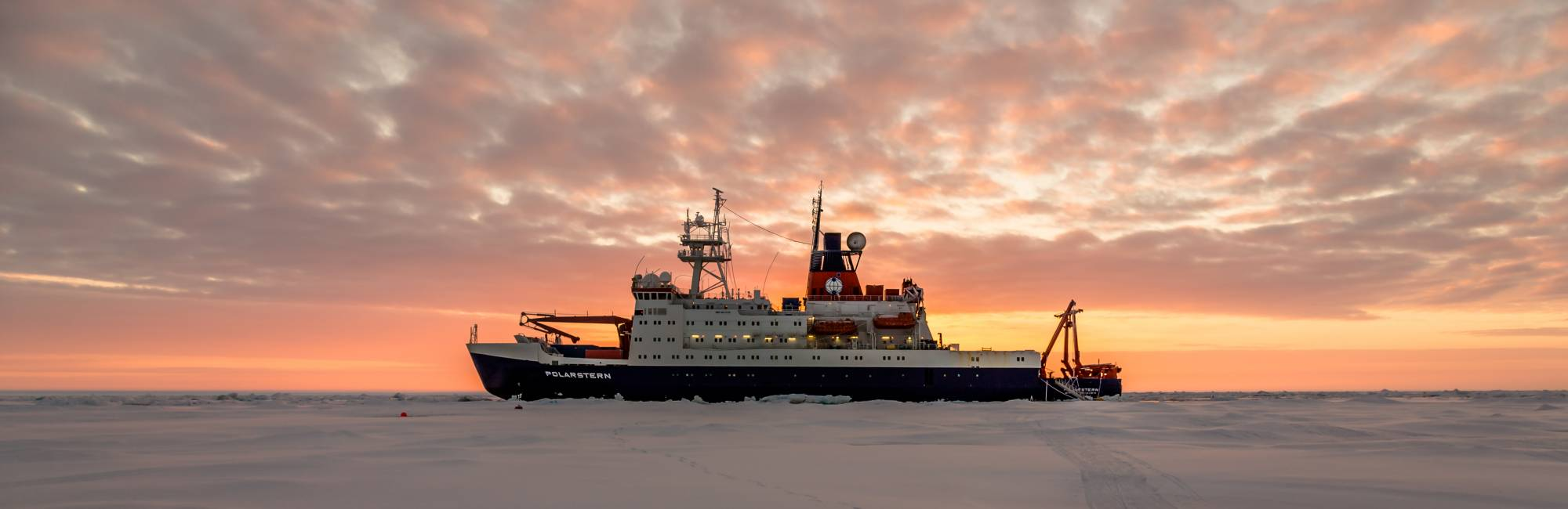 The Polarstern ship parked in Arctic ice at sunset.