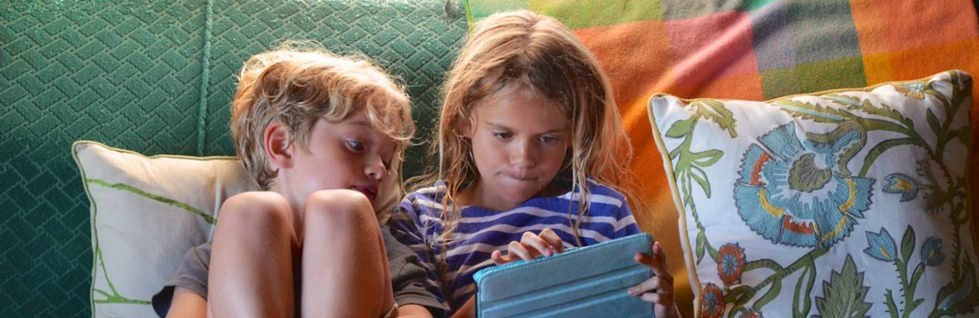 kids on a couch using ipad
