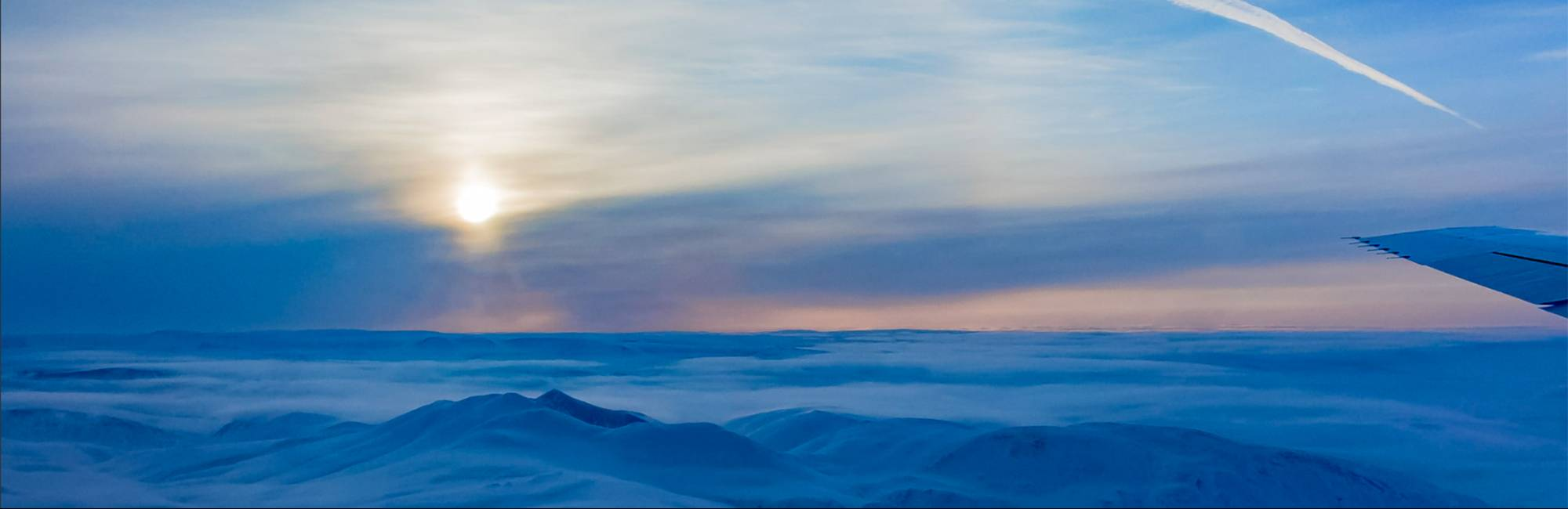 Photo looking out of a NASA DC-8 flying over the Canadian Arctic, with a view of the sun, clouds, and icy mountains.