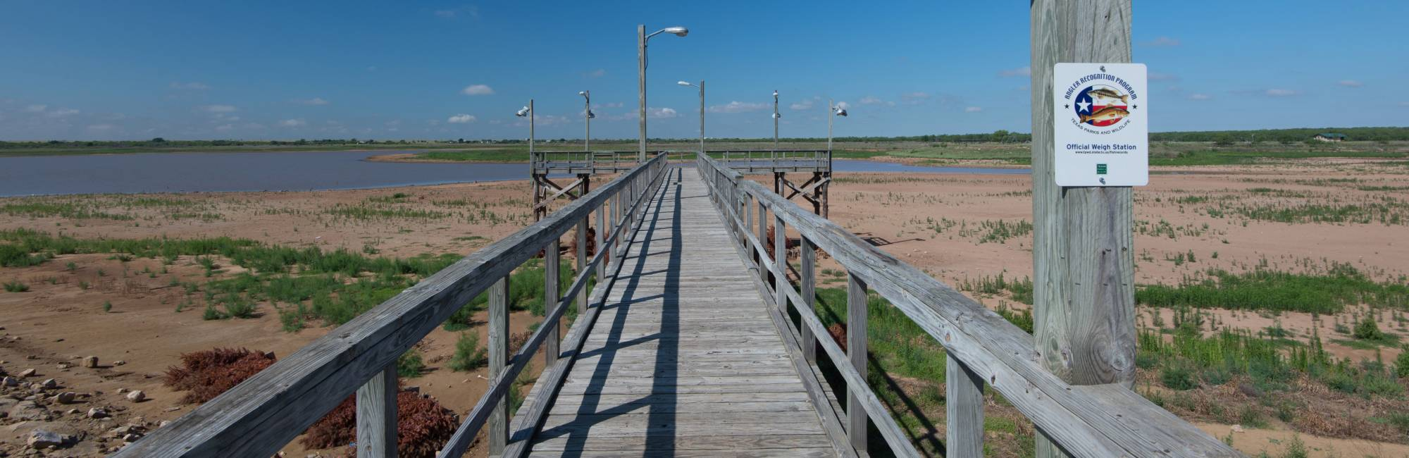 photo of pier surrounded by dry lakebed with lake in the background