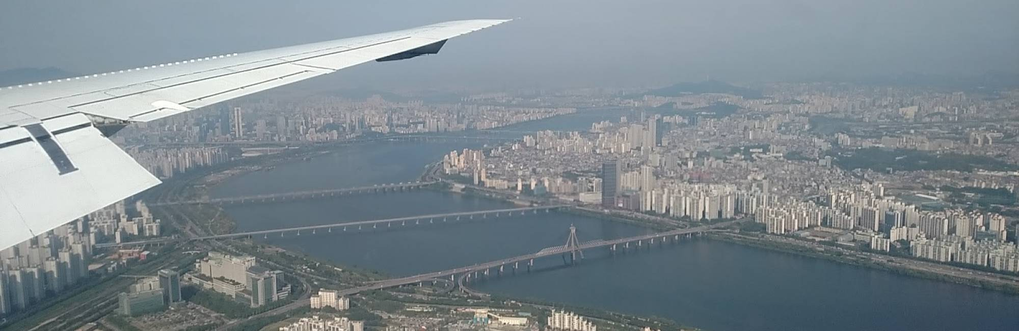 Seoul, seen by air, hazy and with airplane wing in frame