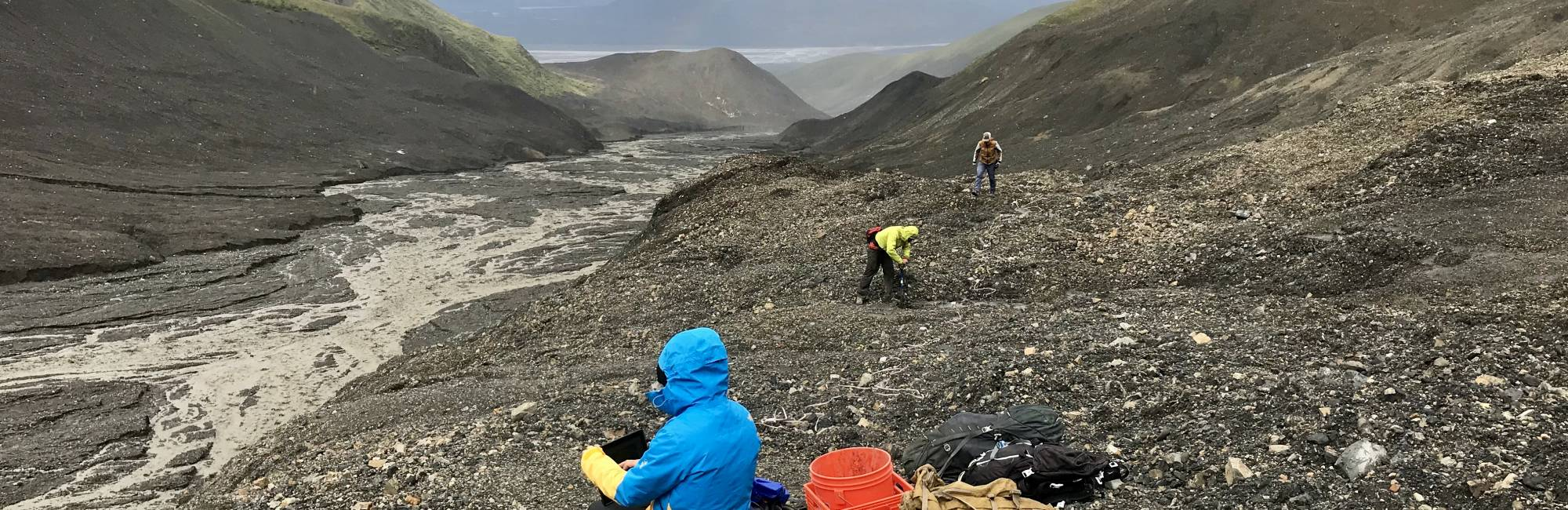 Researchers take measurements in a rocky glacier setting