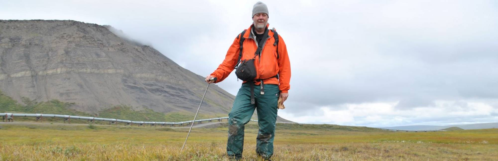 Scientist stands holding tool, in cold grassy landscape