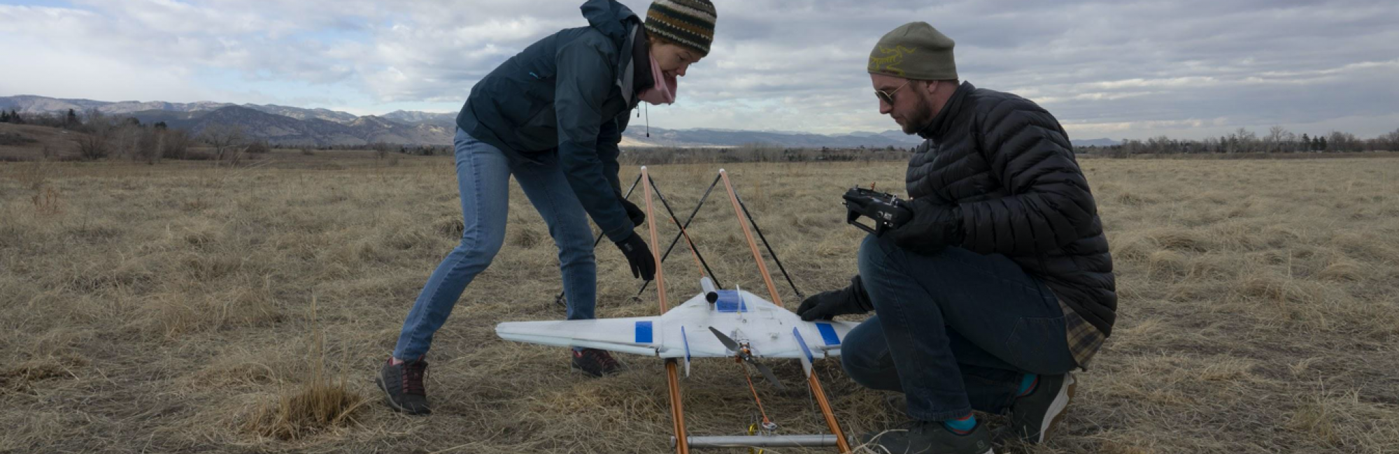 Two people place a DataHawk drone on its launcher in preparation for its first test flight in Boulder, Colorado.