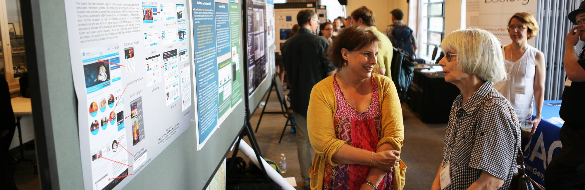 two women talking at a science poster