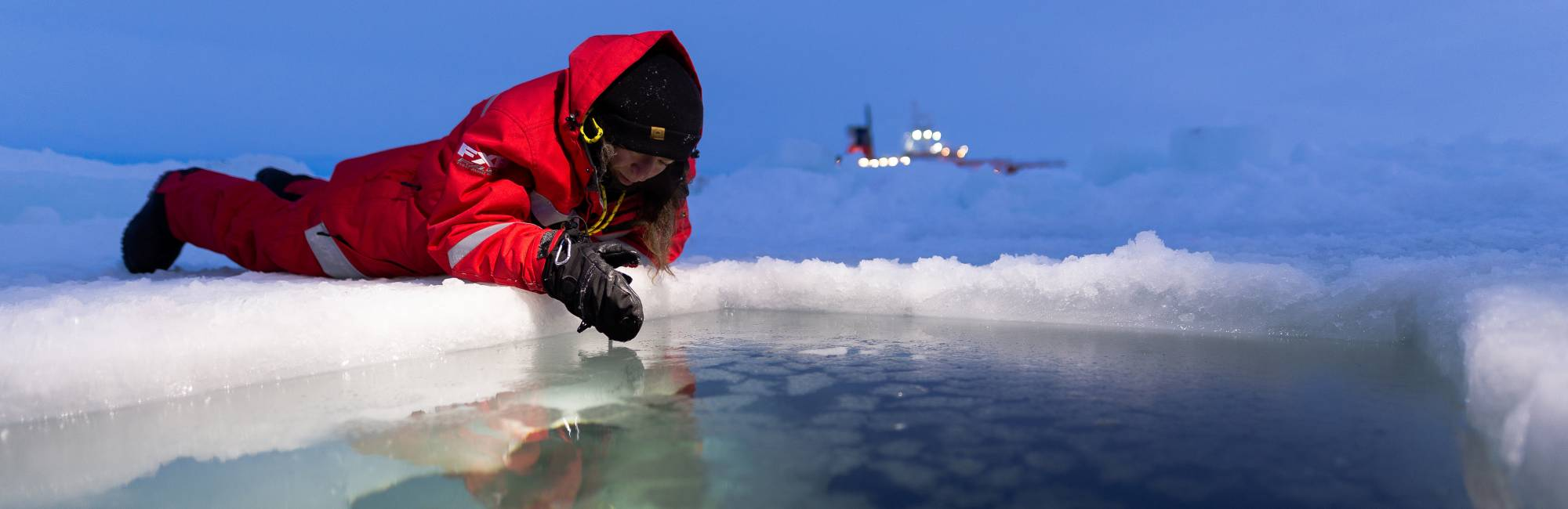 A woman dressed in heavily insulated gear lies on her stomach on the ice, looking into a pool of water. There is an icebreaker ship lit with electric lights far off in the distance.