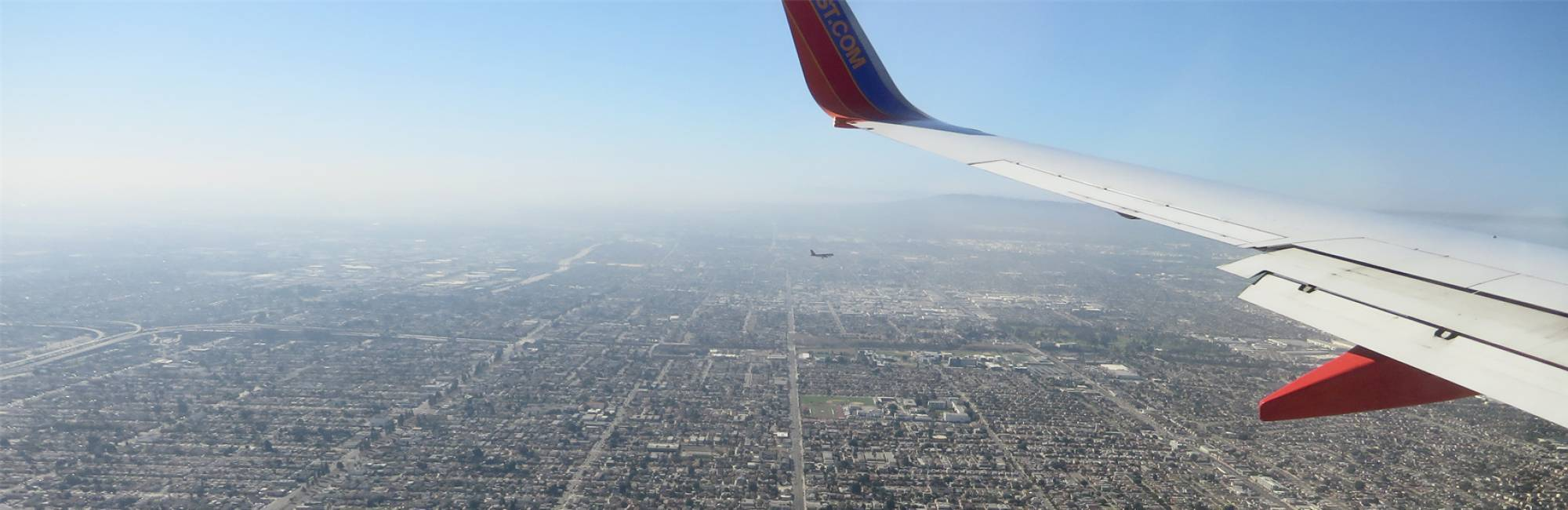 Two planes fly over densely populated Los Angeles as smog blurs the horizon.