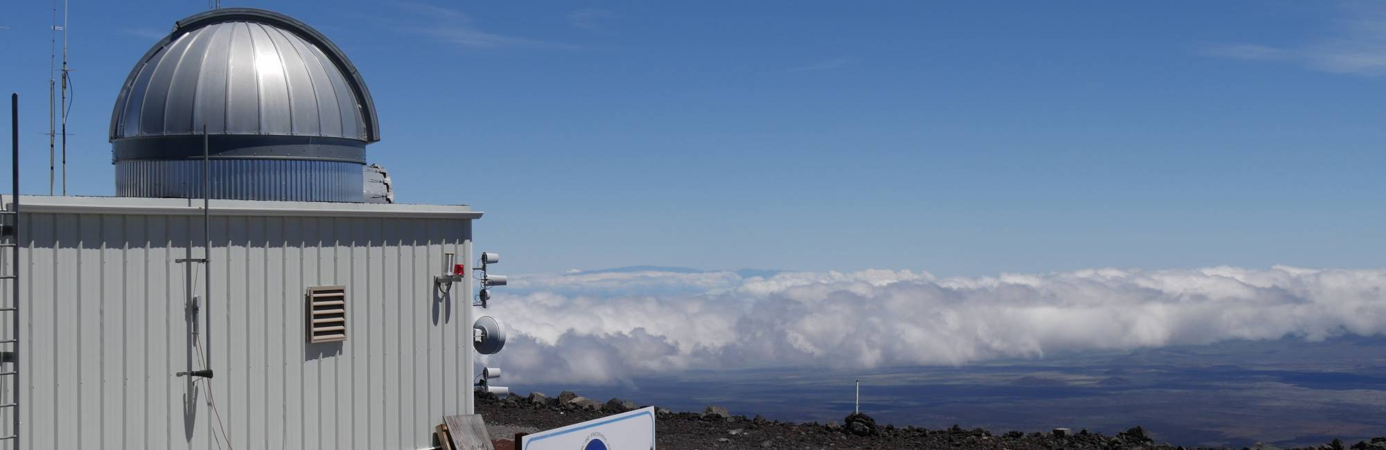 "Photo of NOAA""s Mauna Loa observatory on the barren slopes of a volcano in Hawaii."