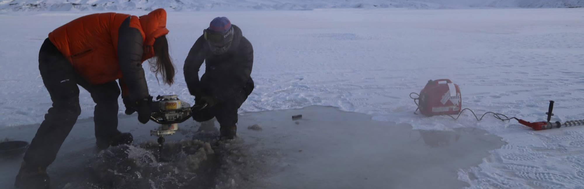 Two researchers use an augur to drill into ice atop a frozen river