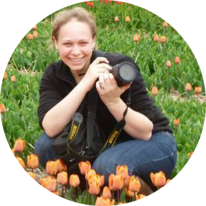 An image of Hannah Holland-Moritz holding a camera in a field of tulips.