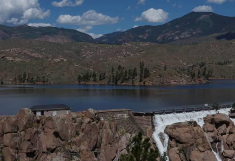 Cheesman Dam spills water down its spillway, a 220-foot high wall of boulders, in June 2019.