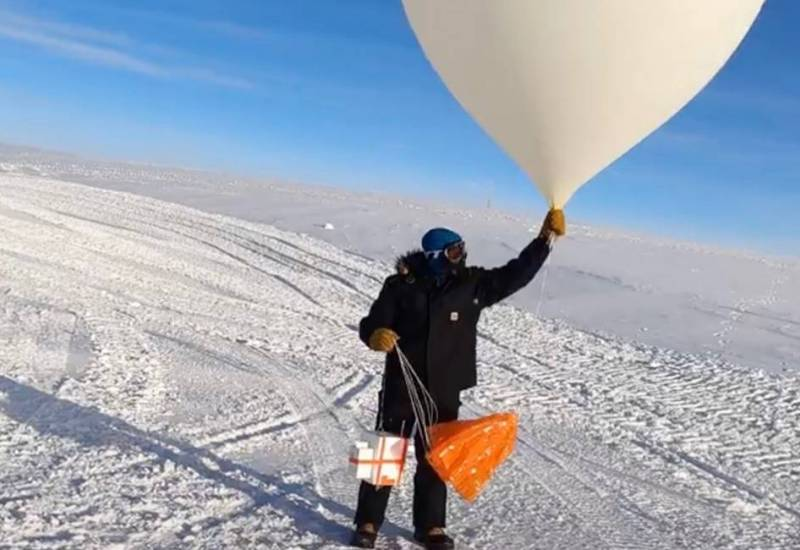 A scientist launches a weather balloon carrying ozone-measuring instruments from the South Pole Station in March of 2021.