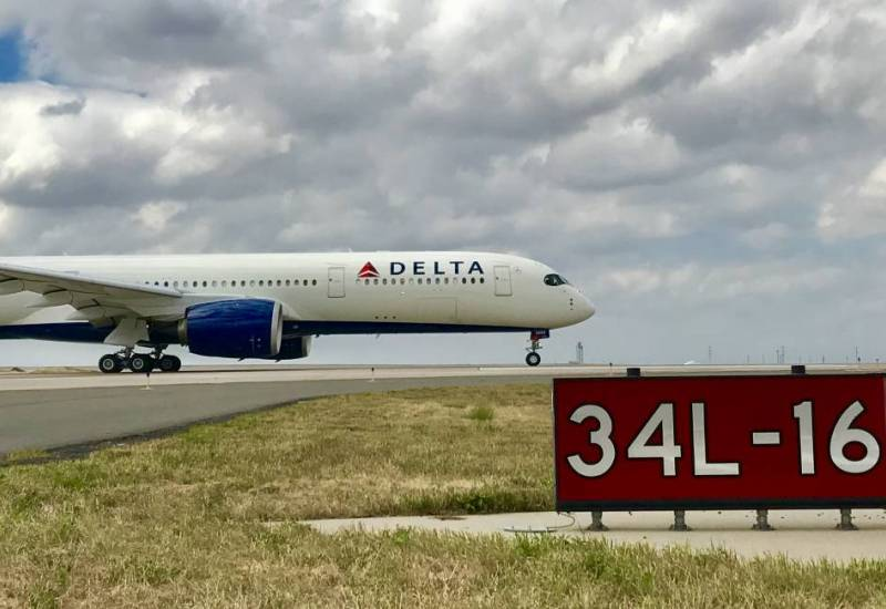 Delta airplane on airport runway with runway marker in foreground