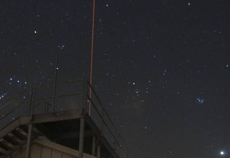 laser light heading up into dark night sky above a building