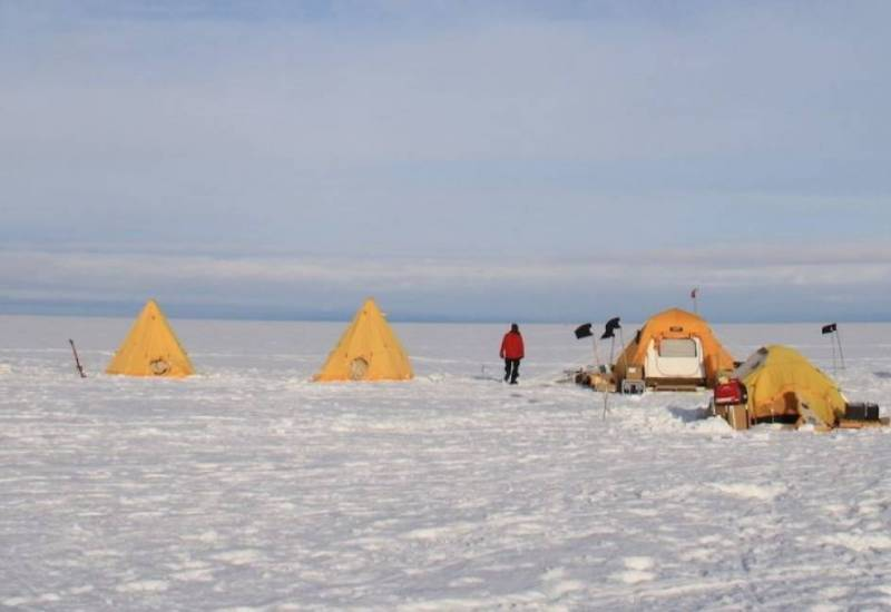 A line of yellow tents set up on a snowy landscape.