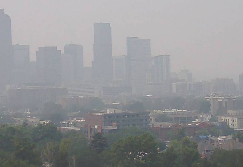 Smoky view of Denver skyline shows outlines of tall buildings almost obscured by haze